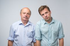 Portrait of two mature men with bored fed up expression, looks displease. Father and son are tired and bored. Portrait of two mature men with bored fed up royalty free stock photos