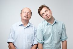 Portrait of two mature men with bored fed up expression, looks displease. Father and son are tired and bored. Portrait of two mature men with bored fed up stock images