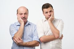 Portrait of two mature men with bored fed up expression, looks displeased up. stock photos