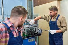 Two Mechanics Fixing Machine at Factory royalty free stock images