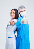 Portrait of a two medical workers showing thumbs up. Isolated on a white background Royalty Free Stock Images