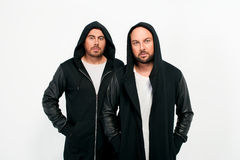 Portrait of two men in black jackets and hoods Stock Photography