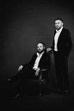 Portrait of two men in black suits monochrome Royalty Free Stock Photo