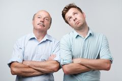 Portrait of two men with bored fed up expression, looks displeased up, being tired to explain their wifes where they were. Portrait of two mature men with bored stock images