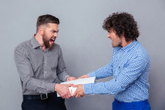 Portrait of a two men fighting for folder Stock Photos