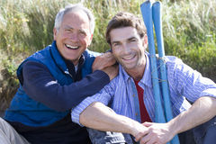 Portrait of two men holding oars on beach stock photos