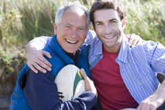 Portrait of two men holding rugby ball on beach royalty free stock images