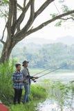 Man sits on the riverbank fishing fish. Portrait of two men on the riverbank fishing fish with friend Royalty Free Stock Photo