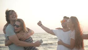 Portrait of Two Men with Their Amazing Girlfriends Smiling and Hugging on the Seaside during Windy Weather. Portrait of Two Men with Their Amazing Girlfriends stock footage