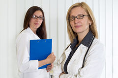 Portrait of Two Middle Age Female Doctors Smiling and Looking at Camera. Half-Length Shot Over White Background Stock Photo