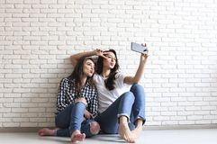 Portrait of two millennial females, fooling around in front of mobile smartphone camera. Brown eyed model girls with long brunette. Two beautiful excited young Royalty Free Stock Photography