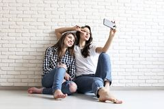 Portrait of two millennial females, fooling around in front of mobile smartphone camera. Brown eyed model girls with long brunette. Two beautiful excited young Stock Photos