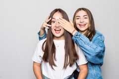 Portrait of two mixed race ladies friends standing isolated over white background. Looking camera covering eyes with hands stock photography