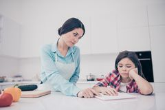 Portrait of two nice cute lovely attractive focused concentrated annoyed bored tired people mature mom helping girl stock photo