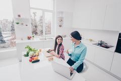 Portrait of two nice cute lovely sweet attractive cheerful cheery people mommy mom working remotely girl making salad in stock photo