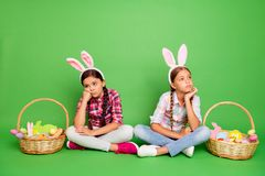 Portrait of two nice lovely sweet sad pre-teen girls wearing checked shirt sitting near festive baskets prepared ready royalty free stock images
