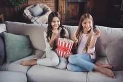 Portrait of two nice sweet lovely attractive lovable fascinating charming cheerful cheery girls sitting on divan stock photo