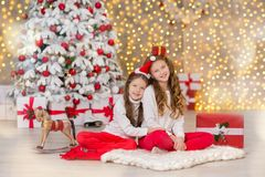 Portrait of two one young girls sisters close to white green Christmas tree. The girls in beautiful evening dresses clothes in New. Year awesome unique Royalty Free Stock Photography