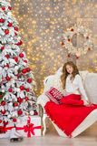 Portrait of two one young girls sisters close to white green Christmas tree. The girls in beautiful evening dresses clothes in New. Year awesome unique Royalty Free Stock Photos