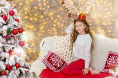 Portrait of two one young girls sisters close to white green Christmas tree. The girls in beautiful evening dresses clothes in New. Year awesome unique Royalty Free Stock Image