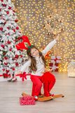 Portrait of two one young girls sisters close to white green Christmas tree. The girls in beautiful evening dresses clothes in New Stock Photo