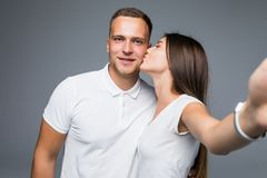 Portrait of two people making selfie while woman kissing her boyfriend in cheek over gray background. Portrait of two people making selfie while women kissing royalty free stock images