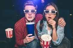 Portrait of two people sitting together in cinema hall and wearing glasses. Girl is amazed and eating popcorn while her. Partner is drinking cola Royalty Free Stock Photography