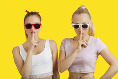 Portrait of two playful young women with fingers on lips over yellow background Stock Photos