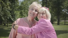 Portrait of two positive old women looking at camera smiling standing in summer park. Leisure girlfriends outdoors