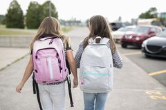 Portrait of two pre teenage girls studying outdoors in school yard left school Royalty Free Stock Photo