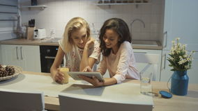 Portrait of two pretty girls using tablet at home. stock footage