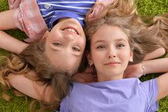 Portrait of two pretty little girls lying on green carpet and looking at camera royalty free stock image