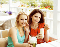 Portrait of two pretty modern girl friends in cafe open air inte Stock Photo