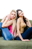 Portrait of two pretty young girlfriends or sisters on sofa Royalty Free Stock Photos
