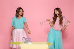 Portrait of a two pretty young girls ironing clothes. On a pressboard while standing with an iron an a magical wand isolated over pink background Royalty Free Stock Photos