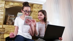 Portrait of two pretty young girls using gadgets at home, friends socializing at home with devices. Portrait of two pretty young girls using gadgets at home stock video