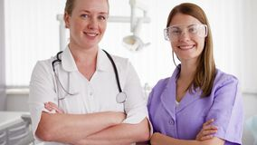 Portrait of two professional female doctors standing in hospital room. Physicians with stethoscope stock video