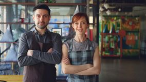 Portrait of two proud small business owners standing inside new spacious cafe and smiling. Successful business start-up
