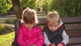 Portrait of two sad children on a park bench. stock footage
