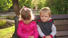 Portrait of two sad children on a park bench. stock video footage