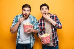 Portrait of a two scared young men eating popcorn. While standing isolated over yellow background stock image