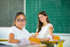 Portrait of two schoolgirls in a classroom. Royalty Free Stock Images