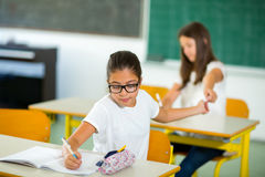 Portrait of two schoolgirls in a classroom. Stock Photos