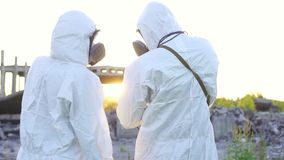 Portrait two scientists in protective suits and masks and a dosimeter , walk measure radiation on the background of the