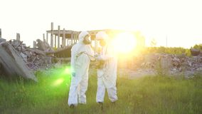Portrait of two scientists in white overalls and protective masks taking measurements of radiation at sunset on the