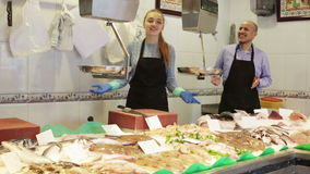 Portrait of two sellers in fish section stock video footage