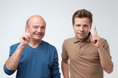 Portrait of two serious mature men father and son with warning finger against light gray background. royalty free stock photo