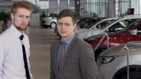 Two men against background of car salon with new models of transport. slow motion. Portrait of two serious men against background of car salon with new models stock video