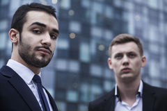 Portrait of two serious young businessmen looking at the camera, outdoors, business district Royalty Free Stock Photos