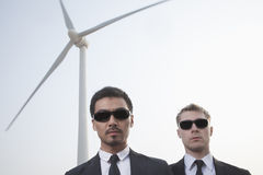 Portrait of two serious young businessmen in sunglasses standing by a wind turbine Royalty Free Stock Photography